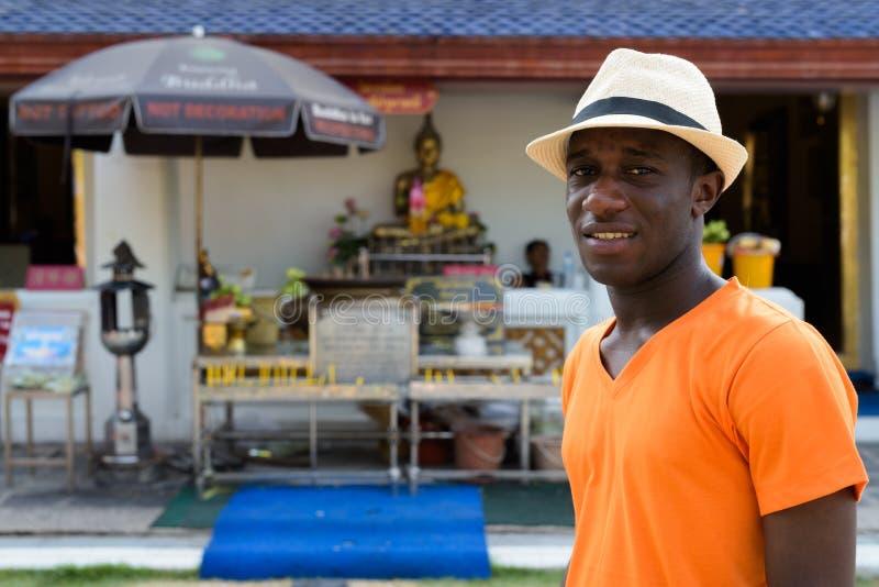 Touristischer Mann des jungen Schwarzafrikaners, der am buddhistischen Tempel lächelt stockfoto