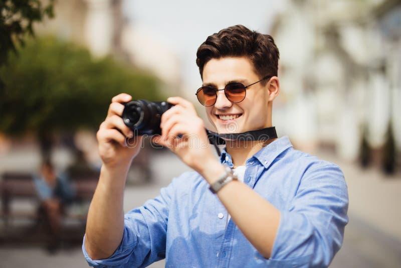 Touristischer Mann mit der Kamera, die Fotos auf Straße macht Porträt des hübschen lächelnden Mannes, der Kamera, Foto von intere lizenzfreies stockfoto