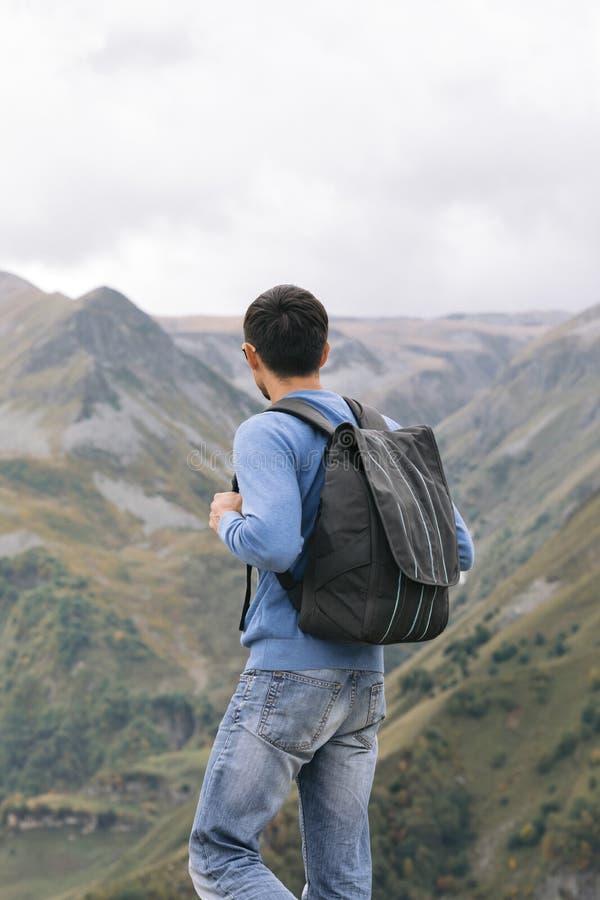 Touristischer Mann mit einem Rucksack gegen den Kaukasus lizenzfreies stockbild