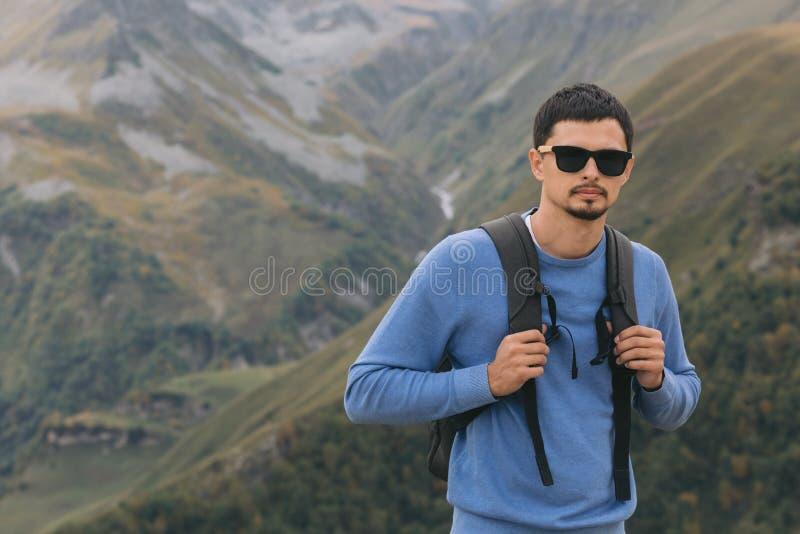 Touristischer Mann mit einem Rucksack gegen den Kaukasus stockfotografie