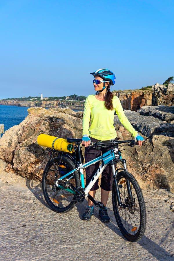 Touristischer Radfahrer der Frau auf dem felsigen Ufer auf dem Leuchtturmhintergrund lizenzfreies stockbild