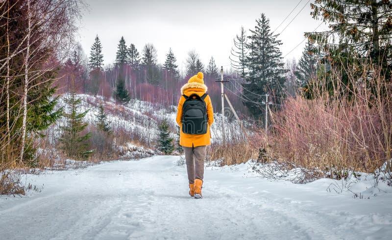 Touristischer Reisender ist Winter im Wald auf einer schneebedeckten Straße lizenzfreie stockbilder