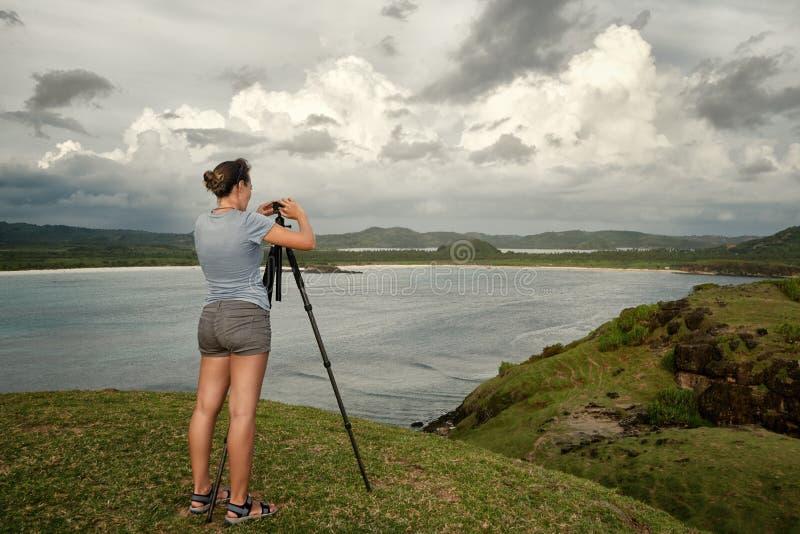 Touristischer Reisendphotograph, der Bilder auf Hintergrundmeer macht stockbild