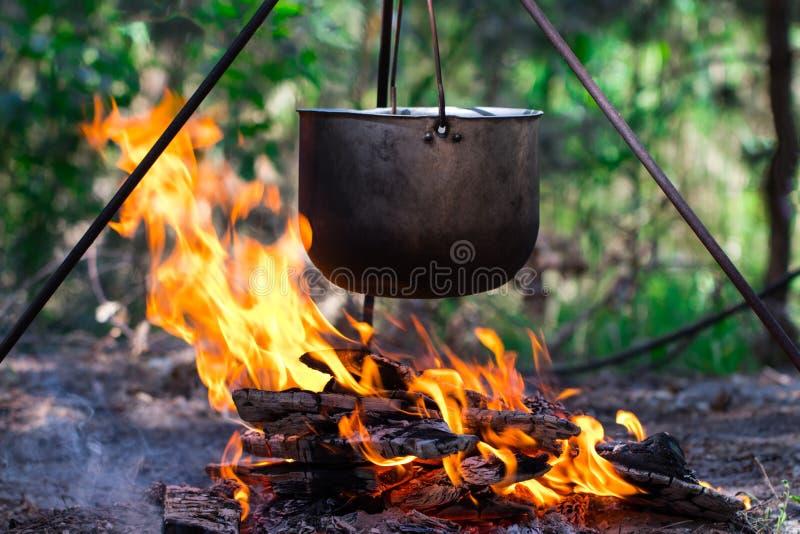 Touristischer Topf, der über dem Feuer auf einem Stativ hängt Kochen im Ca lizenzfreie stockfotos