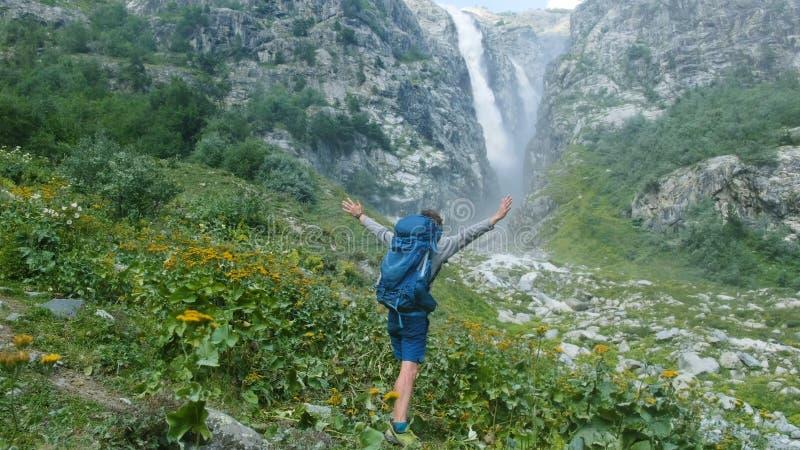 Touristischer Wanderer mit einem Rucksack hebt seine Hände oben an und wendet sich herum selbst gegen den Hintergrund eines enorm stockfotos