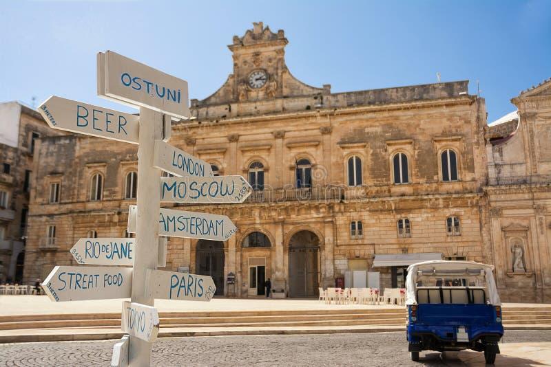 Touristischer Wegweiser mit Abständen und im Hintergrund der Stadtbezirk von Ostuni Italien lizenzfreie stockbilder