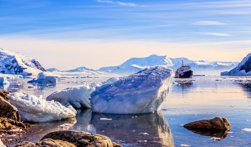 Touristisches antarktisches Kreuzschiff unter den Eisbergen stockfotos