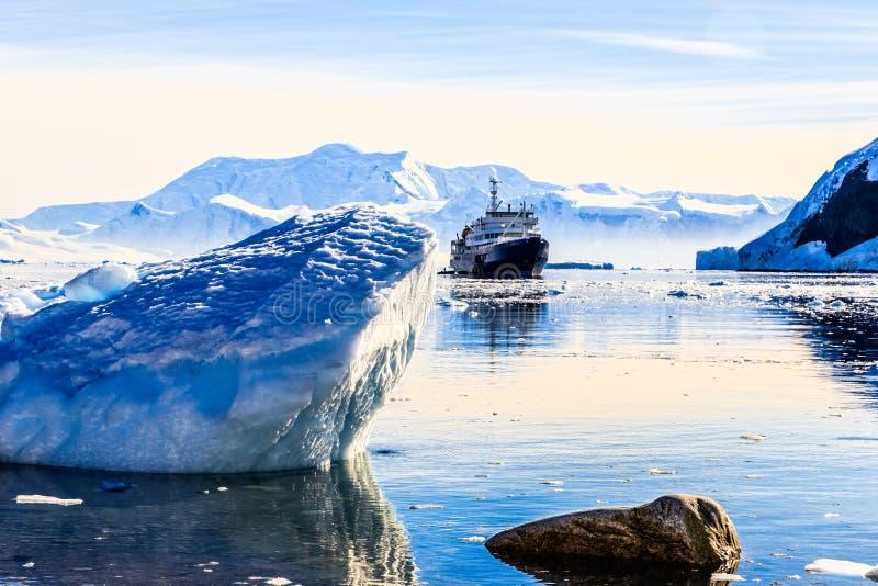 Touristisches antarktisches Kreuzschiff unter den Eisbergen mit Gletscher stockfotografie