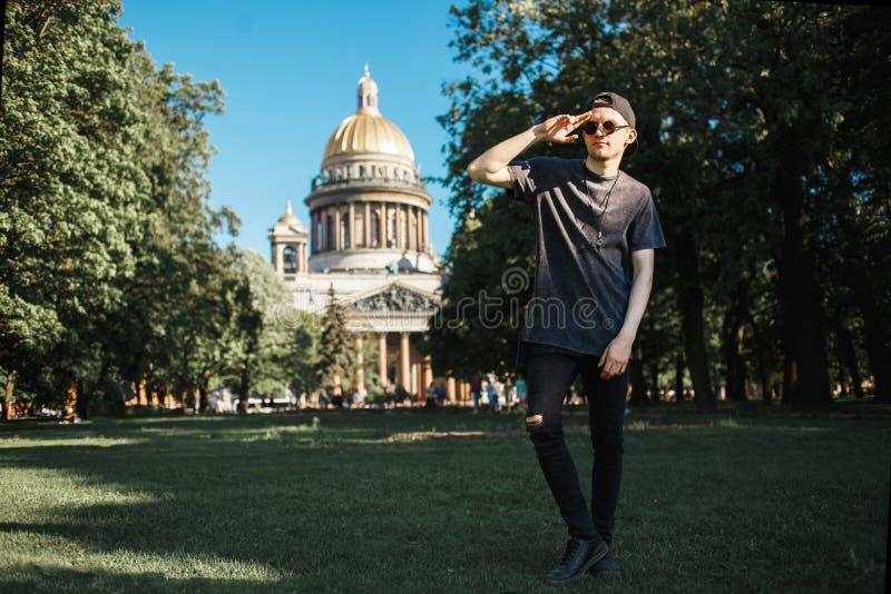 Touristisches Gehen des gutaussehenden Mannes auf Rasen nahe Heilig-Isaac-` s Kathedrale in St Petersburg am sonnigen Sommertag stockfotos