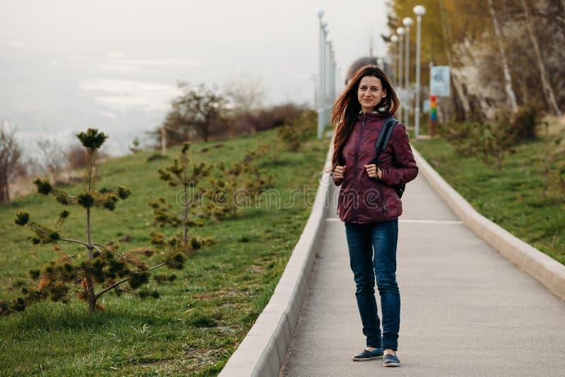 Touristisches lächelndes Gehen der jungen Frau auf die Straße im Park stockfotos