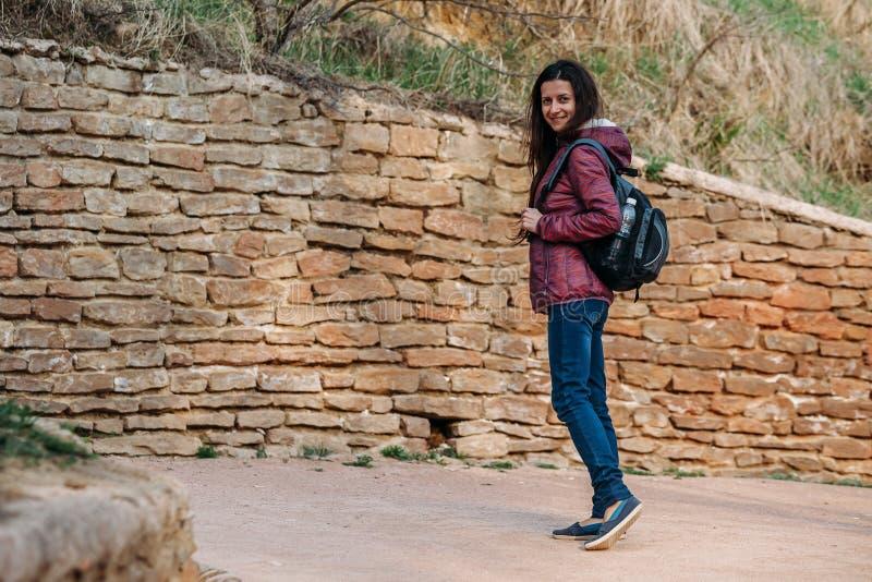 Touristisches lächelndes Gehen der jungen Frau auf Straße im Park lizenzfreie stockbilder
