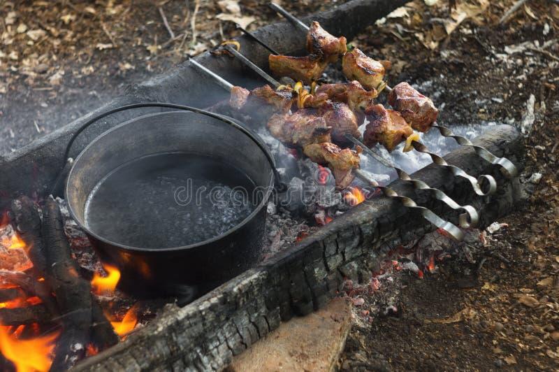 Touristisches Lager der Feldküche auf offenem Feuer des Feuers, des kochenden Wassers im Kessel und gegrillten der Schweinefleisc lizenzfreies stockfoto