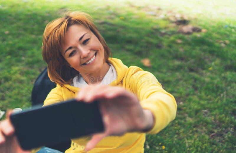 Touristisches Mädchen auf dem grünen Gras des Hintergrundes, das Foto selfie am intelligenten Mobiltelefon, Person schaut auf Kam stockfoto