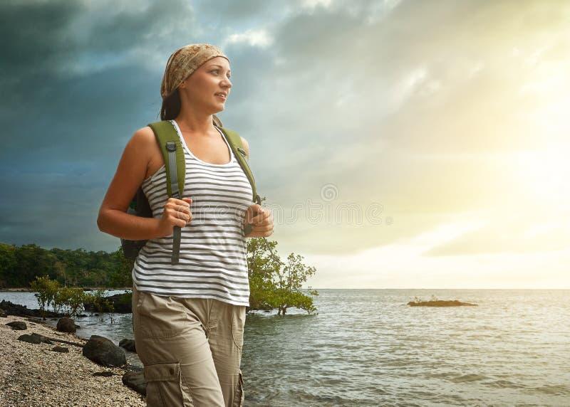 Touristisches Mädchen, das Ansicht des schönen Sonnenuntergangs und des Meeres genießt lizenzfreie stockfotografie