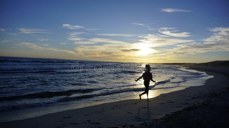 Touristisches Mädchen, das entlang das Meer an einem Sonnenuntergang-Tag in Minorca geht stockbilder