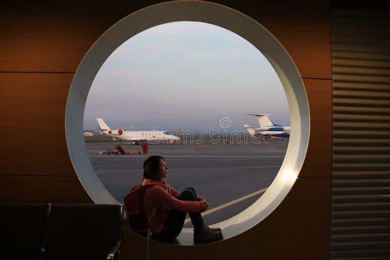 Touristisches Mädchen, das am Flughafenfenster sitzt lizenzfreie stockbilder