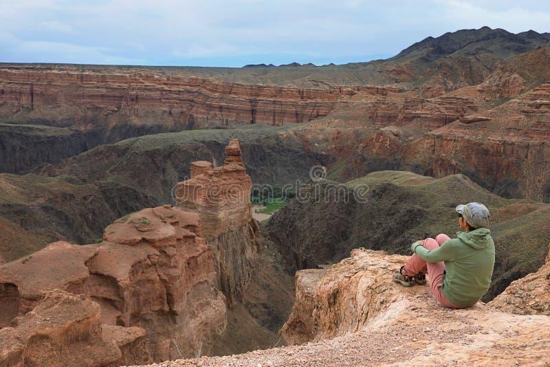 Touristisches Mädchen, das am Rand der Schlucht Charyn sitzt stockfotografie