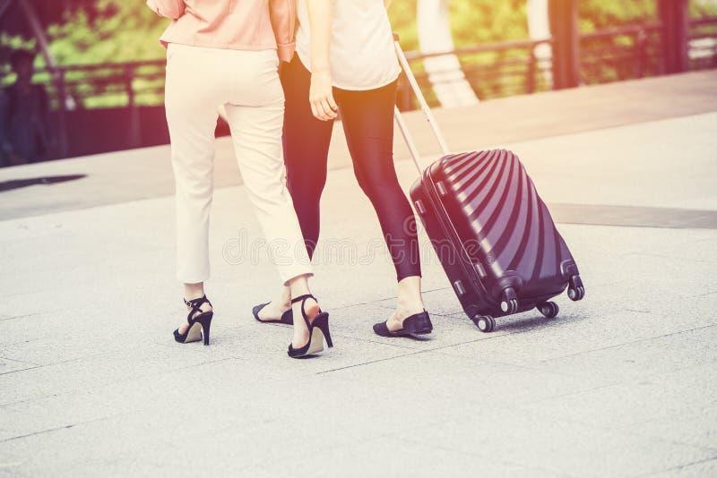 Touristisches Mädchen des Freunds mit zwei Leuten mit dem Reisendgepäckgehen lizenzfreie stockfotos