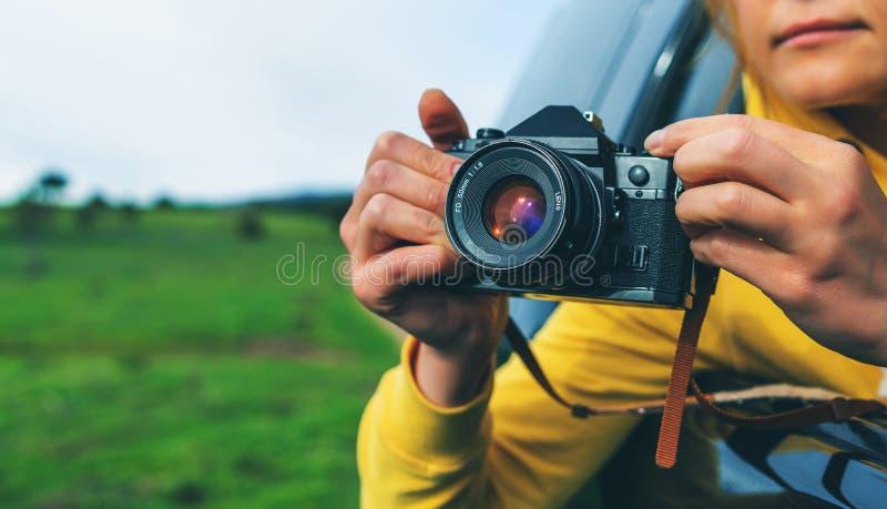 Touristisches Mädchen des Lächelns in einem offenen Fenster eines Selbstautos, das Fotografie nimmt, klicken auf Retro- Weinlesef lizenzfreie stockfotos