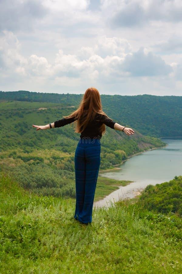 Touristisches Mädchen mit den offenen Armen weit genießt Natur nahe bei einem Gebirgsfluss stockbild