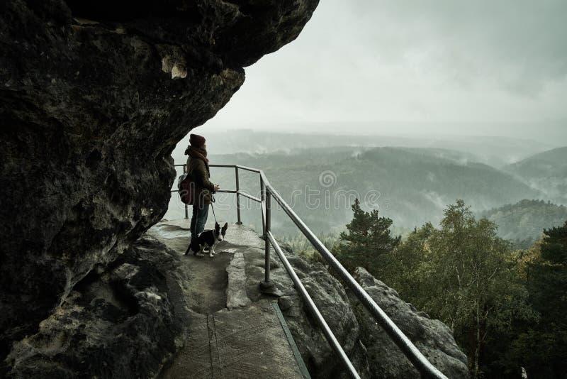 Touristisches Mädchen mit einem Hündchen, das die nebelhaften Nebelberge vom Standpunkt von Bastei in der sächsischen Schweiz, De stockfotos