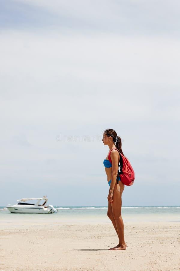 touristisches Mädchen mit einem Rucksack durch das Meer stockbilder