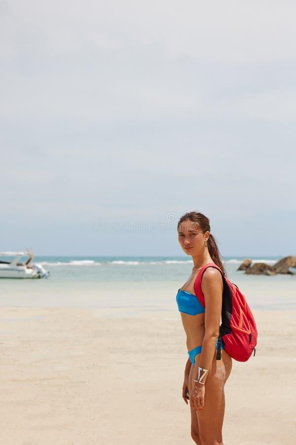 touristisches Mädchen mit einem Rucksack durch das Meer lizenzfreie stockbilder