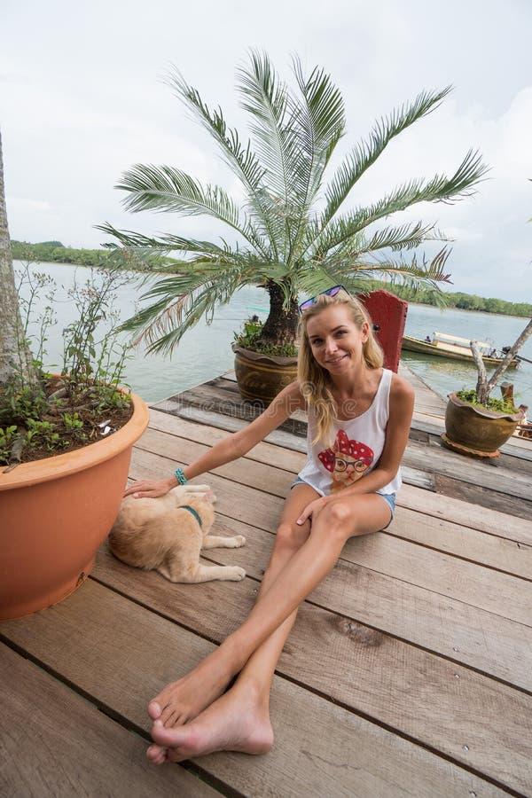 Touristisches Mädchen streichelt Ingwerkatze am Pier in Koh Panyee lizenzfreie stockfotos