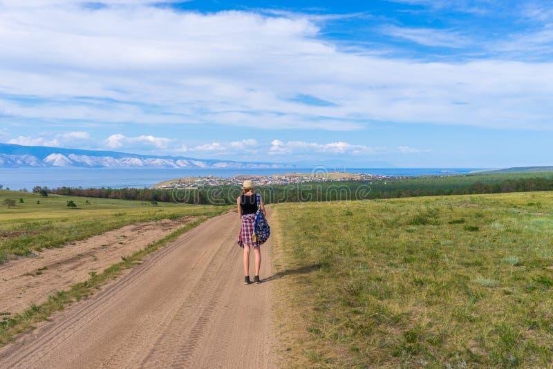 Touristisches M?dchen des Tweens im Hut und im Rucksack gehend auf Landstra?e allein und malerische Landschaft vom Baikalsee, Ber stockfotos