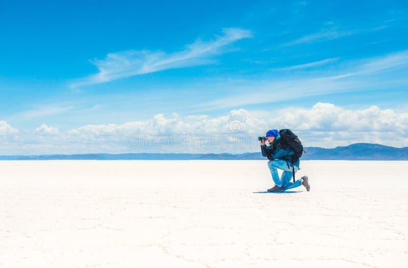 Touristisches nehmendes Foto im Sonnenschein Salar de Uyuni lizenzfreie stockbilder