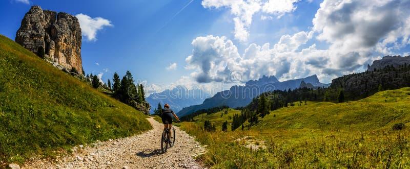 Touristisches Radfahren in Cortina d'Ampezzo, erstaunliche felsige Berge auf dem Hintergrund Frau, die MTB-enduro Flussspur reite lizenzfreie stockbilder