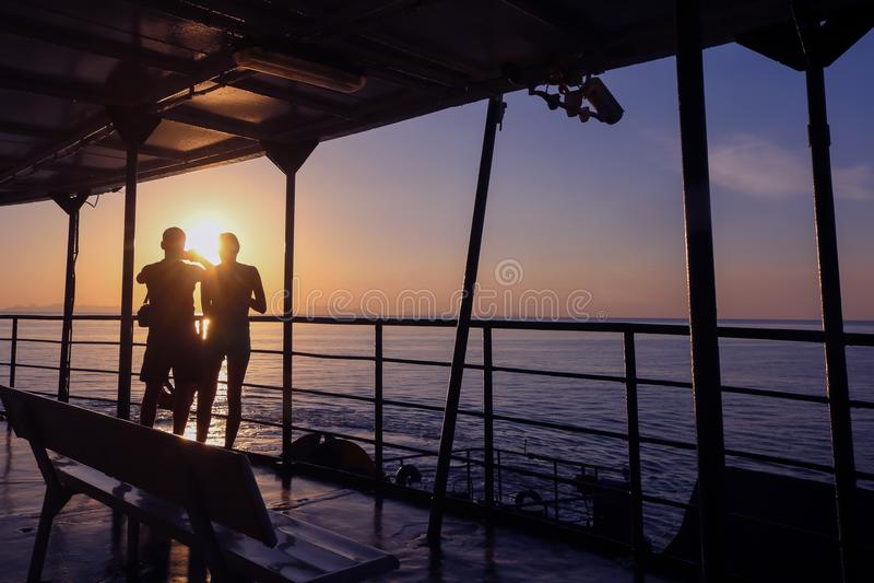 Touristisches schauendes Sonnenlicht der Paare teilt an das Meer auf der Fähre mit stockfoto