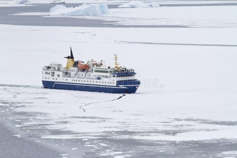 Touristisches Schiff, das Eis in der Straße des antarktischen Peninsu bricht stockbilder
