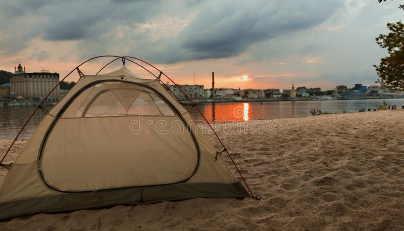 Touristisches Zelt trifft den Sonnenuntergang auf dem Stadtstrand des Dnipro-Flusses in Kiew, Ukraine lizenzfreie stockbilder