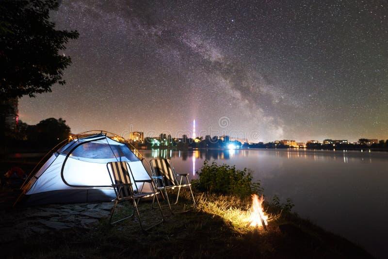 Touristisches Zelt, zwei kampierende Stühle und Lagerfeuer auf Seeufer nachts lizenzfreies stockfoto
