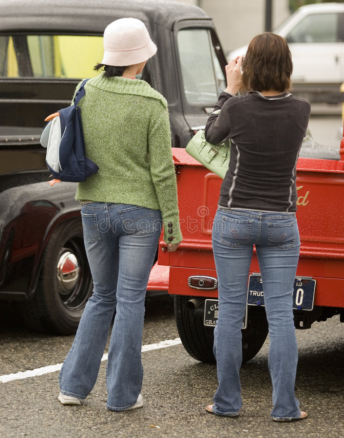 Tourists. Rear view of two girls snaping photos at a collector's car show stock photos