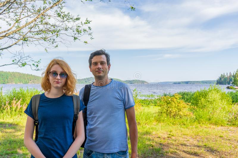Tourists adult man and teenage girl posing against beautiful landscape in summer sunny day. Portraits of father and daughter on royalty free stock image
