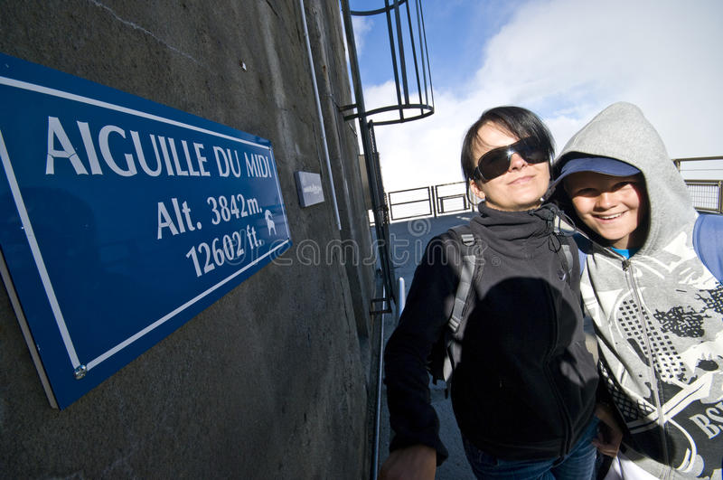 Tourists at Aiguille du Midi, France. Two tourists (mother and teenage son) standing at information board of Aiguille du Midi peak and view point, between royalty free stock photo