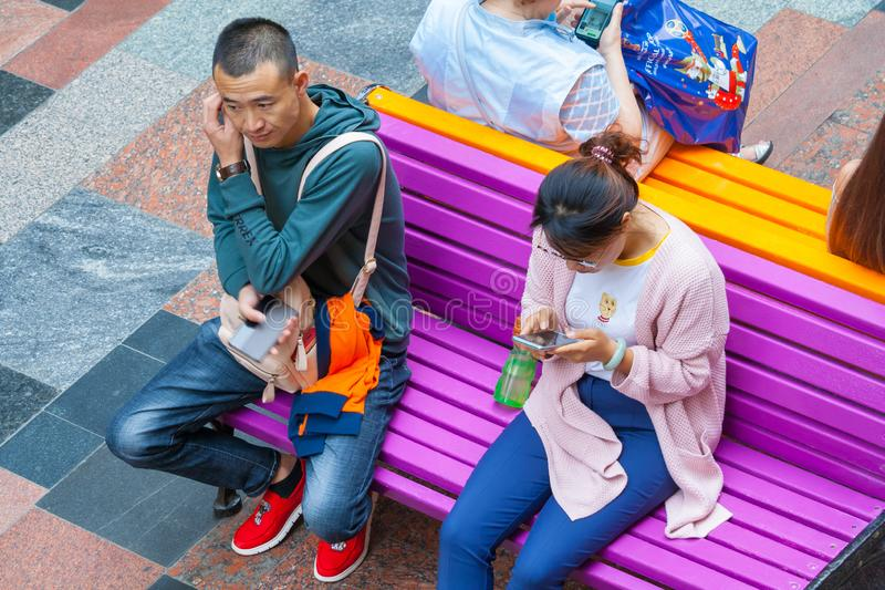 Tourists from Asia are sitting on a bench with phones editorial stock photo