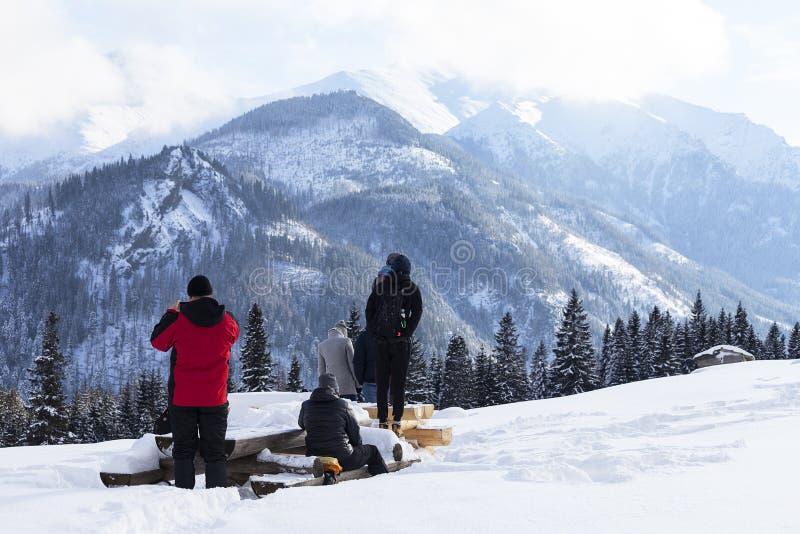 Tourists on the background of High Tatra Mountains in a winter snowy day, Tatra Mountains, Rusinowa Polana, Poland stock image