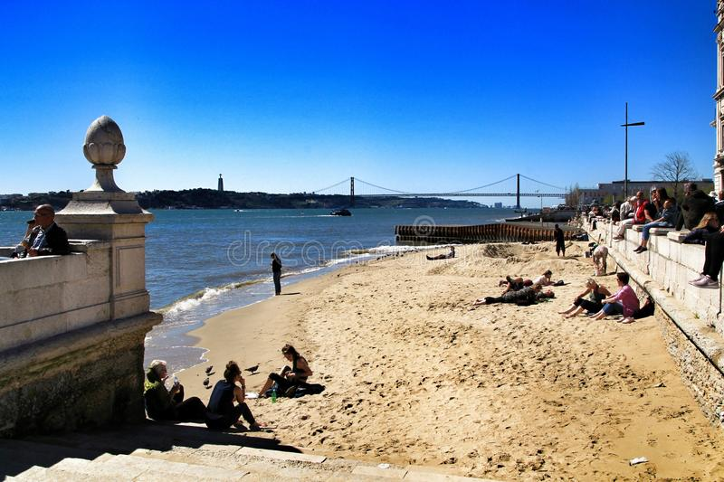 Tourists on the banks of Tagus river in Lisbon royalty free stock photo