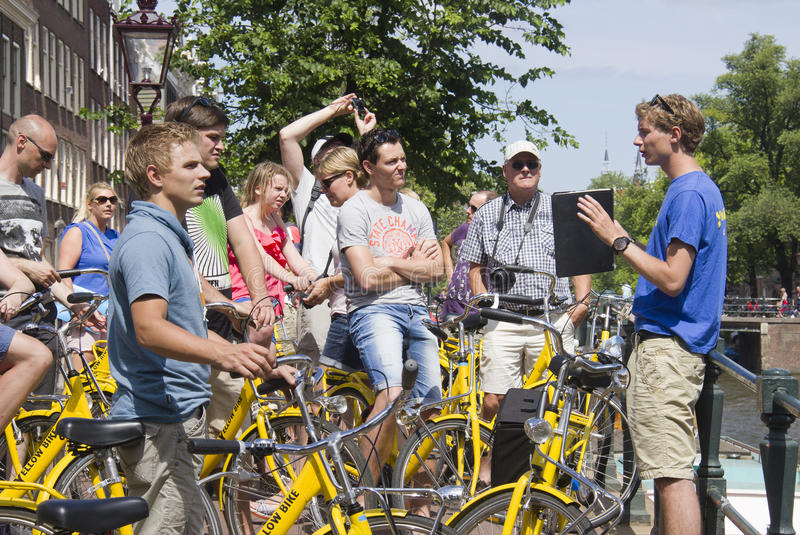 Tourists on bikes in Amsterdam. Amsterdam, Holland - July 19, 2013: Group of tourists with yellow bikes listen to their guide on a canal in front of the Anne stock images