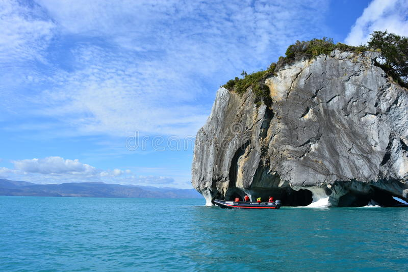 Tourists in a boat in front of Capillas de Mármol rock formations, Chile royalty free stock photo