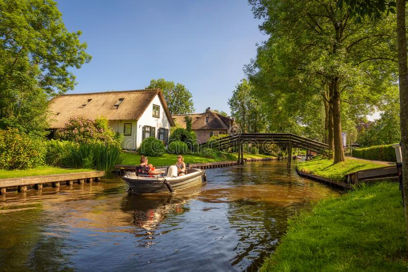 Tourists on a boat in the village of Giethoorn, Netherlands. Giethoorn, Netherlands - May 30, 2018 : Tourists on a boat in the dutch village of Giethoorn royalty free stock images