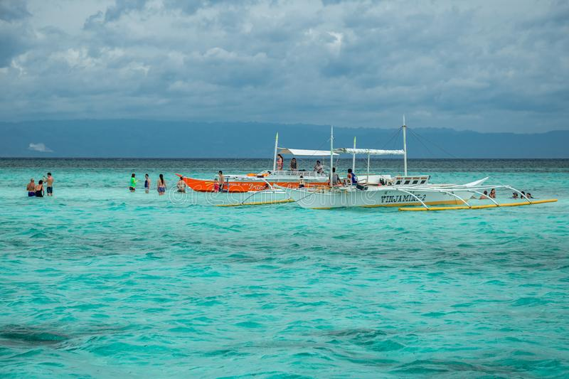 Tourists and boats in the azure sea on the small Virgin island of Panglao, Bohol, Philippines. August 2018. Tourists and boats in the azure sea on the small royalty free stock photo