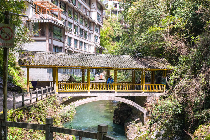 Tourists on bridge over gorge with creek. JIANGDI, CHINA - MARCH 26, 2017: tourists on bridge over gorge with creek near spa resort hotels in Longsheng Hot royalty free stock photography