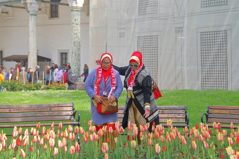 Tourists in bright clothes admire tulips. ISTANBUL, TURKEY - APRIL 20, 2019. The photo was taken in the park of Istanbul. The picture shows two middle-aged royalty free stock photos