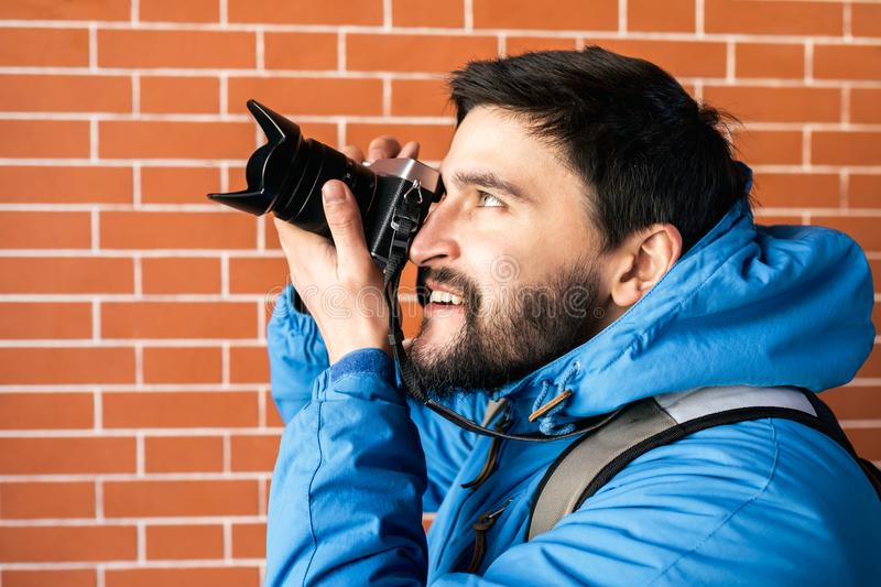 Tourists with camera in the city. Brick wall background. Portrait of happy young man. Tourists with camera in the city. Brick wall background stock images