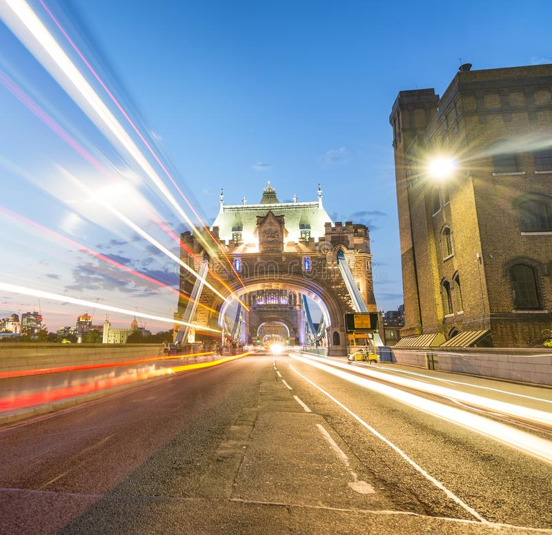 Tourists and car light trails at night along Tower Bridge, London in summer royalty free stock photo