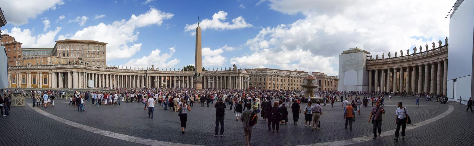 Tourists on central square. Vatican City, Vatican - April 10, 2010: tourists on central square Piazza San Pietro of city or capital with colonnades, obelisk and royalty free stock images